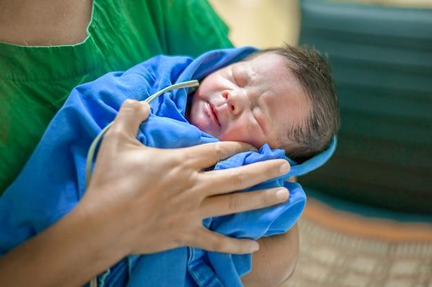 Pasgeboren baby van een dag oud: een pasgeboren baby ligt in de armen van een verpleegster na de bevalling in een verloskamer van een ziekenhuis.