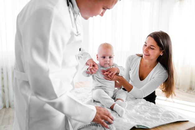 Pasgeboren baby vastgehouden door arts en moeder