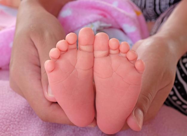Pasgeboren baby voet in handen van moeder.