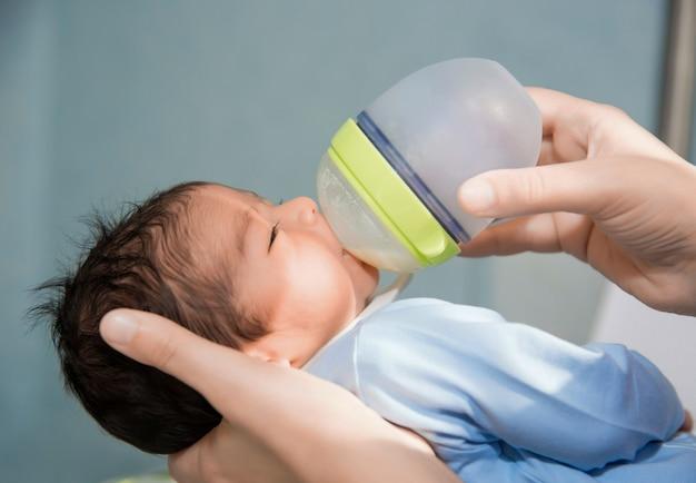 Pasgeboren baby wordt gevoed uit een klein flesje in het ziekenhuis