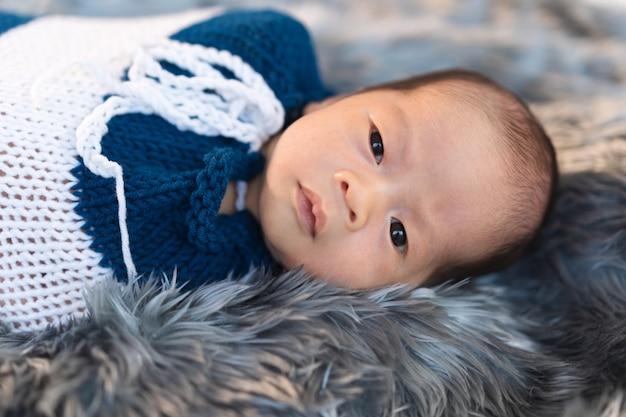Pasgeboren babyjongen gewikkeld in een gebreide omslag op bontbed