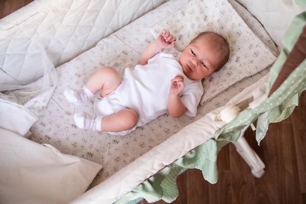 Pasgeboren babyjongen in bed. pasgeboren kind in witte bodykit die in lichte wieg ligt