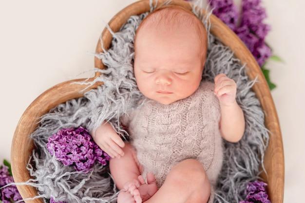 Pasgeboren babyjongen met een gebreid beige kostuum dat in een houten hartvormig bed met bloemen ligt en slaapt. schattig baby kind dutten