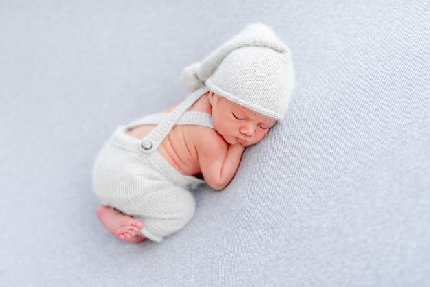 Pasgeboren babyjongen met een gebreide broek en muts die op zijn buik slaapt en kleine handjes onder zijn wangen houdt. schattig baby kind dutten in studio met lichtblauwe kleuren