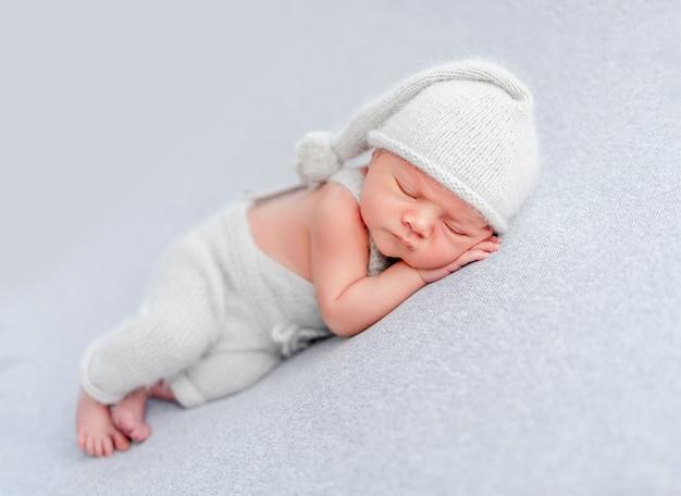 Pasgeboren babyjongen met een gebreide broek en muts die slaapt en kleine handjes onder zijn wangen houdt. schattig baby kind dutten in studio