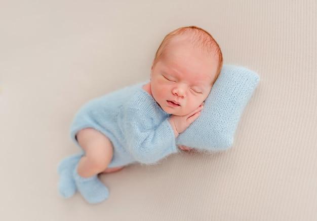 Pasgeboren babyjongen met gebreid kostuum en sokken die op kussen slapen en kleine handen onder zijn wangen houden. schattig baby kind dutten