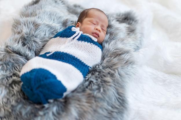 Pasgeboren babyjongen slaapt en gewikkeld in een gebreide wrap op bed