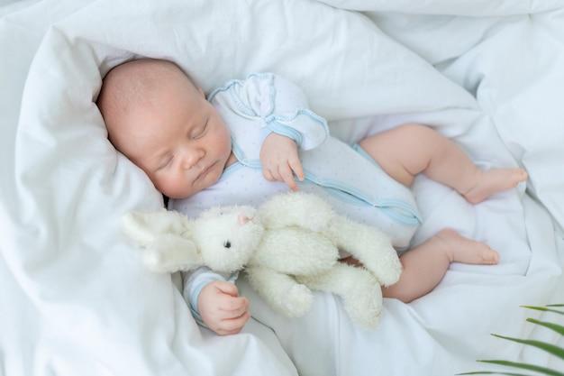Pasgeboren babyjongen slaapt zeven dagen in een wieg thuis op een katoenen bed met een speeltje in zijn hand, close-up. Premium Foto