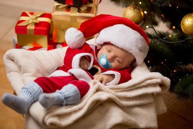 Pasgeboren babyjongen slapen in de woonkamer bij de kerstboom en dozen met cadeautjes