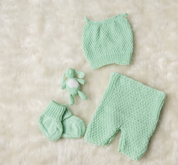 Pasgeboren babykleding, pasgeboren kindermuts, sokken, slofjes, broeken, schoenen op wit