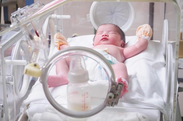 Pasgeboren babymeisje binnen incubator in de kamer van de postbezorging van het ziekenhuis