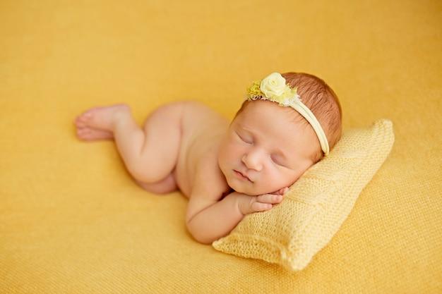Pasgeboren babymeisje, in slaap op een gele deken