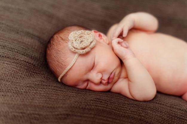 Pasgeboren babymeisje met bloem op hoofd op bruine oppervlakte