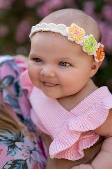 Pasgeboren babymeisje met roze gebreide kleding en een hoofdtoebehoren onder bloemen