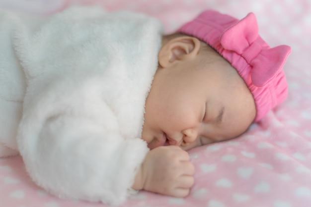 Pasgeboren babymeisje slapen op bed