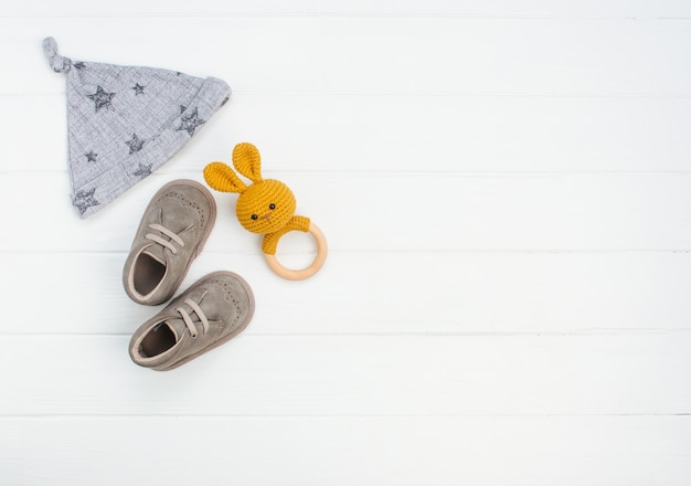 Pasgeboren babymutsje, schoenen en konijn zitzak op witte houten