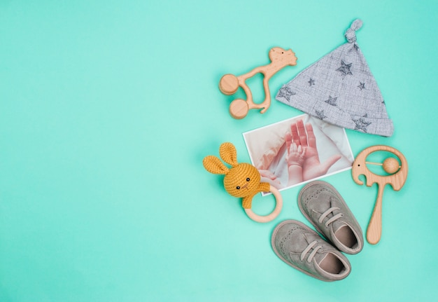Pasgeboren babymutsje, schoenen en speelgoed op turkoois