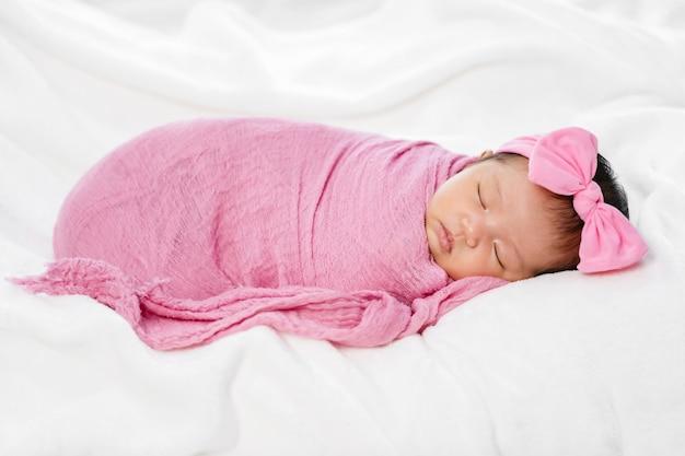 Pasgeboren babyslaap in de roze deken van de doekomslag op een bed