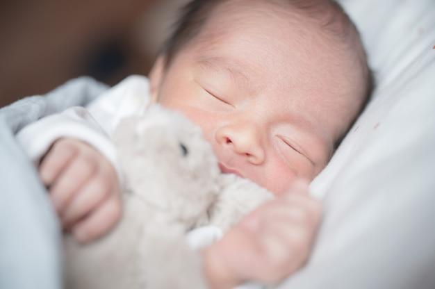Pasgeboren babyslaap op bed met weinig konijn. familie en liefdeconcept. aziatisch jong geitje.