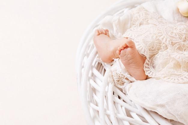 Pasgeboren babyvoetjes op opengewerkte plaid. close-up foto. de voetenclose-up van uiterst kleine pasgeboren baby.