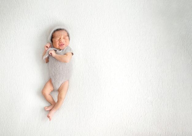 Pasgeboren heeft een verfrommeld gezicht baby fronst en begint te huilen met een uitdrukking van een ontevreden gevoel baby gekleed in een grijze garenjurk en wollen muts op geïsoleerde grijsachtig witte achtergrond schot bovenaanzicht