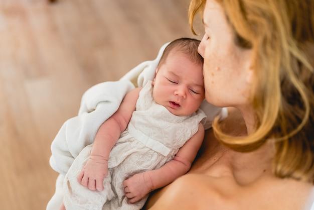 Pasgeboren in de armen kijkt naar zijn moeder.