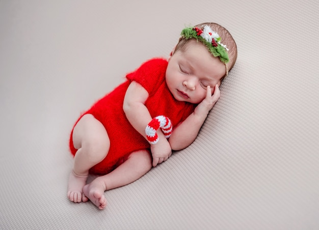 Pasgeboren in rood pak met gebreide kerstsnoepjes