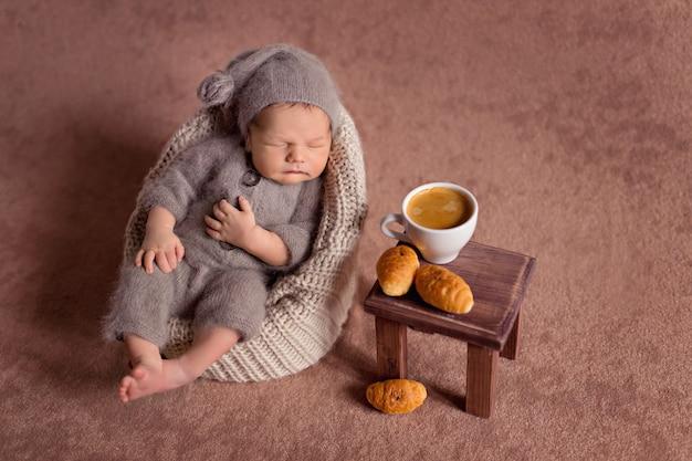 Pasgeboren jongen slaapt in een gebreid kostuum