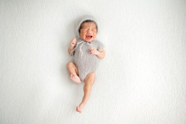 Pasgeboren luid huilend met opgewonden stem die een gevoel van honger naar moedermelk uitdrukt baby gekleed in een grijze garenjurk en wollen hoed op geïsoleerde grijsachtig witte achtergrond schot bovenaanzicht