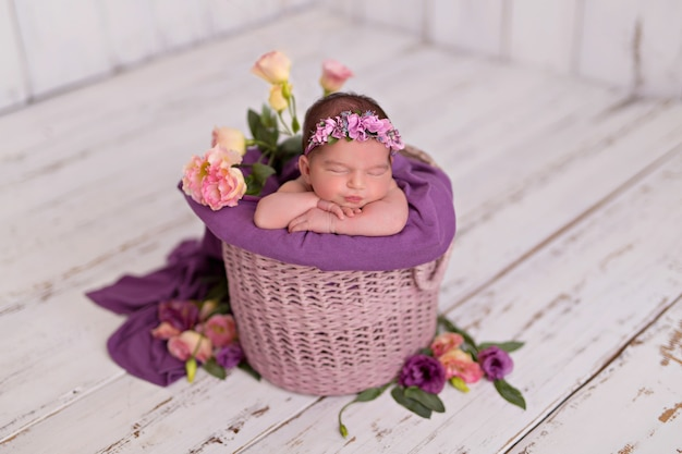 Pasgeboren meisje, baby slaapt in een emmer met bloemen.