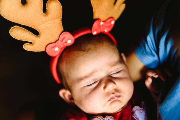 Pasgeboren meisje in slaap met een hoed van de kerstman