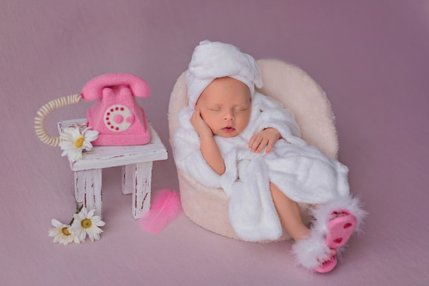 Pasgeboren meisje na spa-behandelingen ligt in een fauteuil in een badjas en roept op een roze telefoon