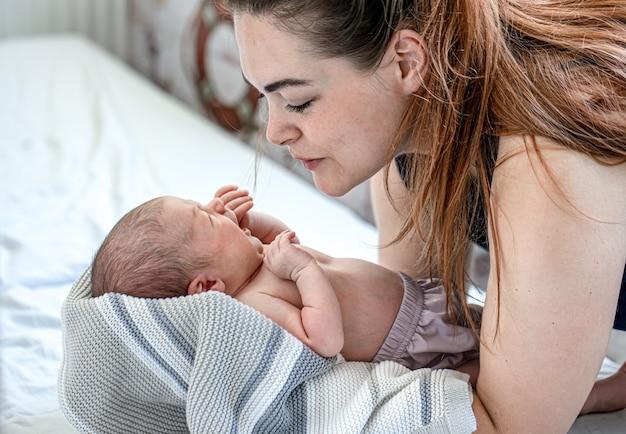 Pasgeboren peuter huilt in moeders armen in de slaapkamer.