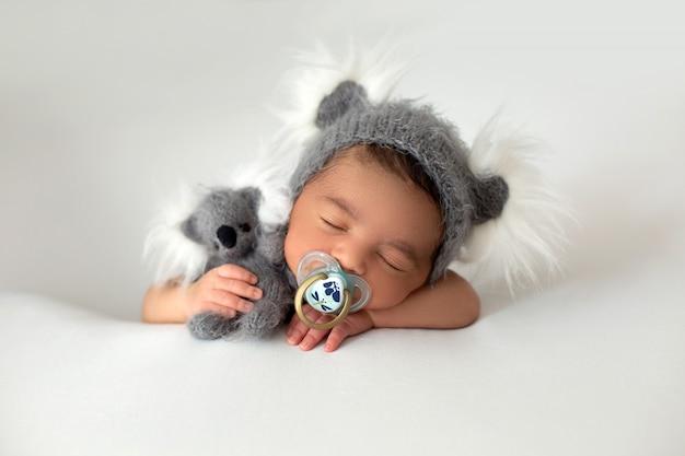 Pasgeboren schattige babyboy draagt weinig rustende baby met grijze hoed en grijs stuk speelgoed in zijn hand en fopspeen op zijn mond op een witte vloer