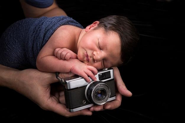 Pasgeboren slapende baby met oude camera