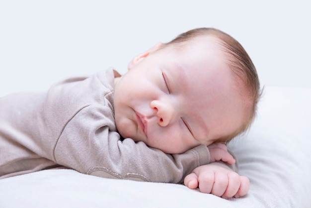 Pasgeboren slapende baby op buik op lichte achtergrond