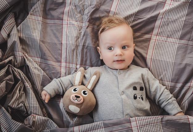 Pasgeboren tot vier maanden oud liggend op het bed met een speelgoedhaas