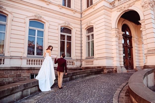 Pasgetrouwden bij de ingang van het paleis met een oude architectuur