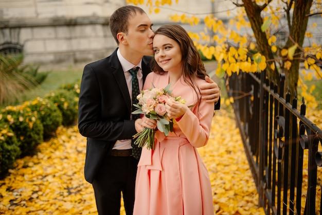 Pasgetrouwden bruidegom en bruid wandelen in herfst park in de buurt van vintage sfeer gotische kathedraal. bruiloft, liefde concept.