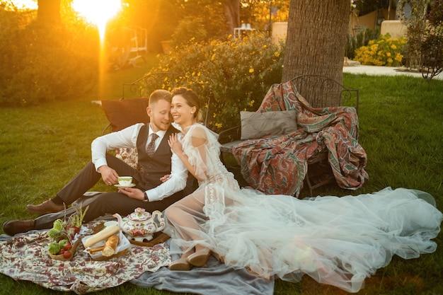 Pasgetrouwden diner op het gazon bij zonsondergang. een paar zit en drinkt thee bij zonsondergang in frankrijk