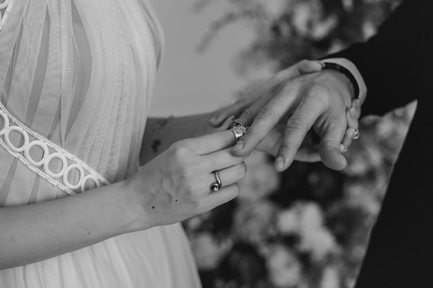 Pasgetrouwden doen elkaar ringen op de bruiloft