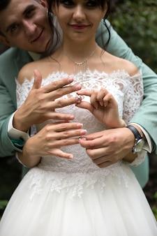 Pasgetrouwden dragen elkaar gouden ringen. echtgenoten