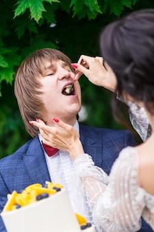 Pasgetrouwden en bruidsmeisjes hebben plezier en eten samen bruidstaart in de frisse lucht op een bruiloftsbanket.