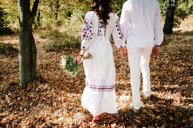 Pasgetrouwden gaan terug kijken in het herfstpark. oekraïense stijl: vrouw, man in geborduurde kleding met boeket bloemen lopen over de natuur. etnisch huwelijk in klederdracht.