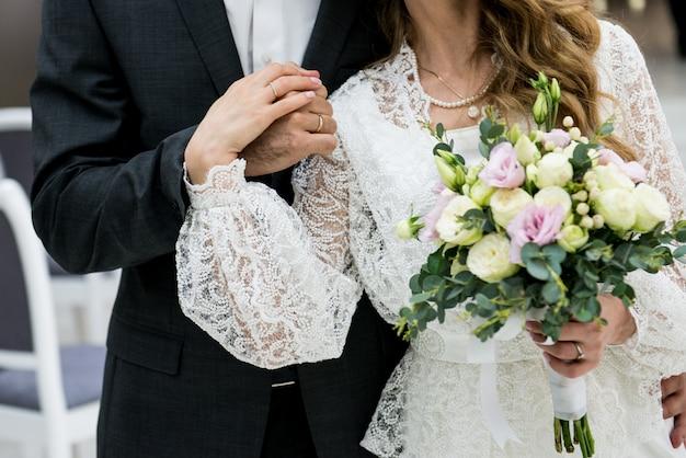 Pasgetrouwden houden elkaars hand vast. handgemaakte bruidjurk. bruiloft. bruid en bruidegom met een boeket.