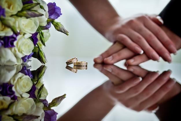 Pasgetrouwden houden elkaars hand vast naast de trouwringen die op het spiegeloppervlak liggen