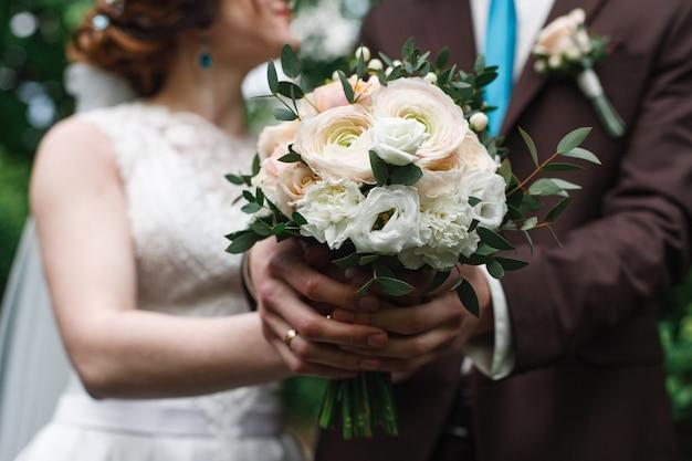 Pasgetrouwden houden handen binnenshuis. bruiloft boeket van roze en witte rozen. trouwdag. huwelijk