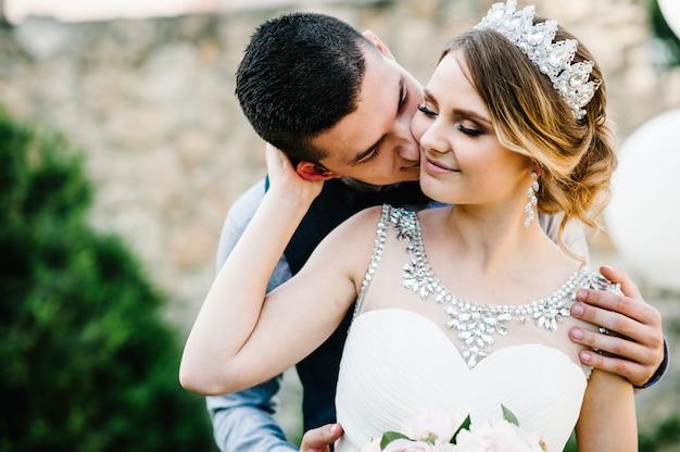 Pasgetrouwden knuffelen en kussen. een man omhelst een vrouw van achteren en kust zijn wang.