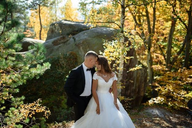 Pasgetrouwden knuffelen in het herfstbos