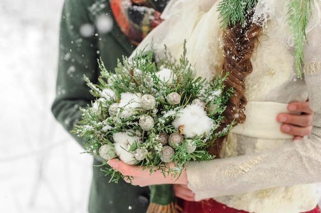 Pasgetrouwden knuffelen in het winterbos. verliefd stel. winter huwelijksceremonie.